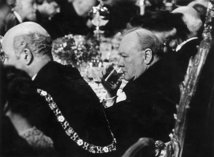 Winston Churchill takes a drink at a luncheon