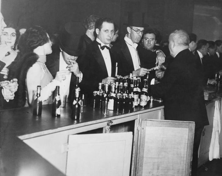 November 1931: Evening dressed revellers buying their drinks at a bar at the time of prohibition