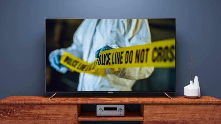 "A television with a person in a hazmat suit pulling yellow tape that reads ""police line do not cross."""
