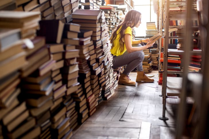 A woman sits and reads among piles of books.