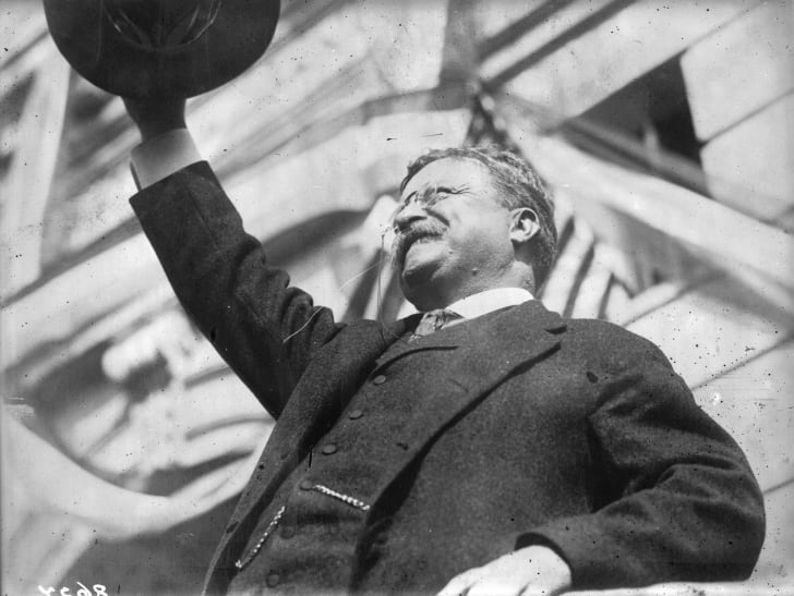 President Theodore 'Teddy' Roosevelt salutes a crowd during a public appearance