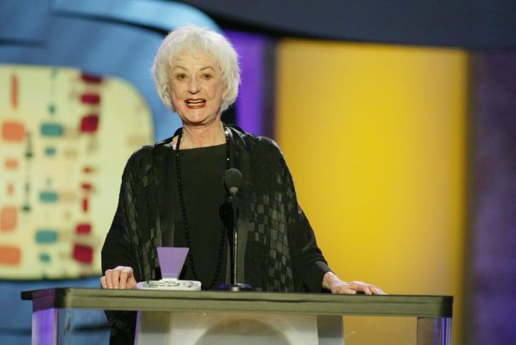 Bea Arthur at a podium on stage.