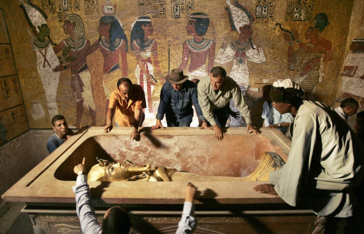 Archaeologists surrounding sarcophagus in King Tut's tomb.