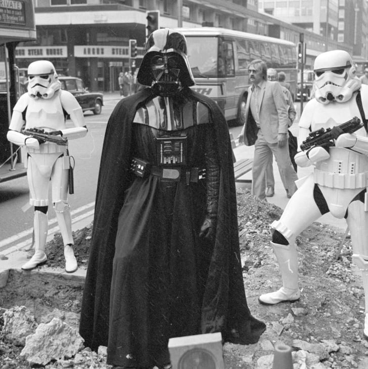 Darth Vader and two stormtroopers from the film 'Star Wars' stand menacingly over some road works in London's Oxford Street in 1980.