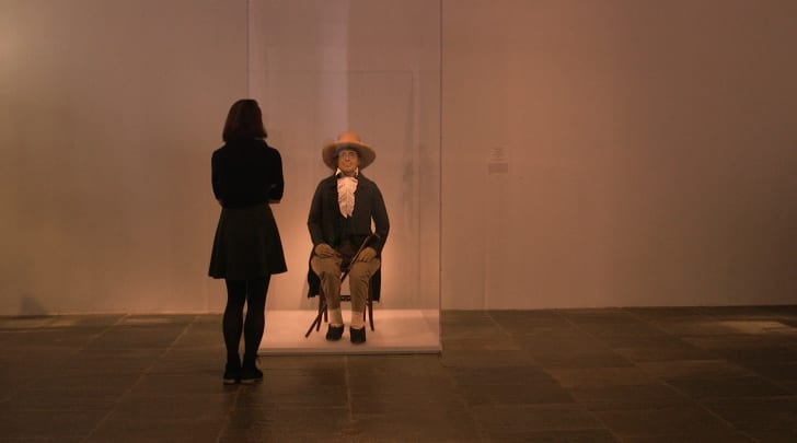 The back of a woman gazing at Jeremy Bentham's auto-icon