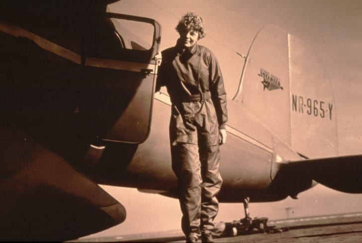 Amelia Earhart in front of plane.