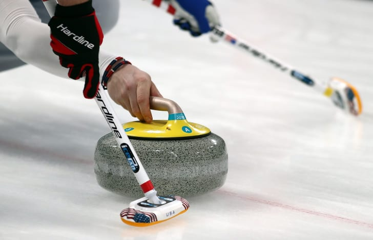 Throwing curling stone across the ice.