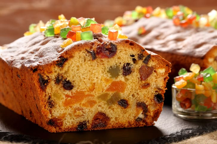 A sliced fruitcake covered in candied fruits sits on a stone cutting board.