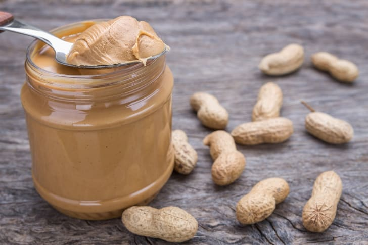 Spoon with peanut butter on top of a jar surrounded by peanuts.