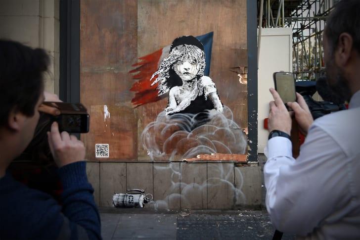 People photograph a Banksy artwork opposite the French embassy