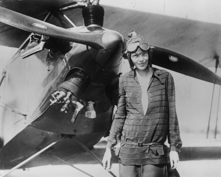 Amelia Earhart stands in front of an airplane in a black-and-white photo. She wears aviator goggles and a cap.