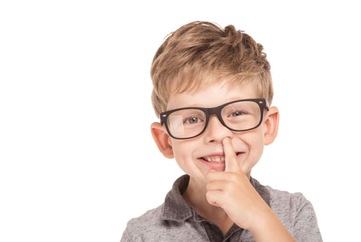 Photo of young boy in glasses picking his nose