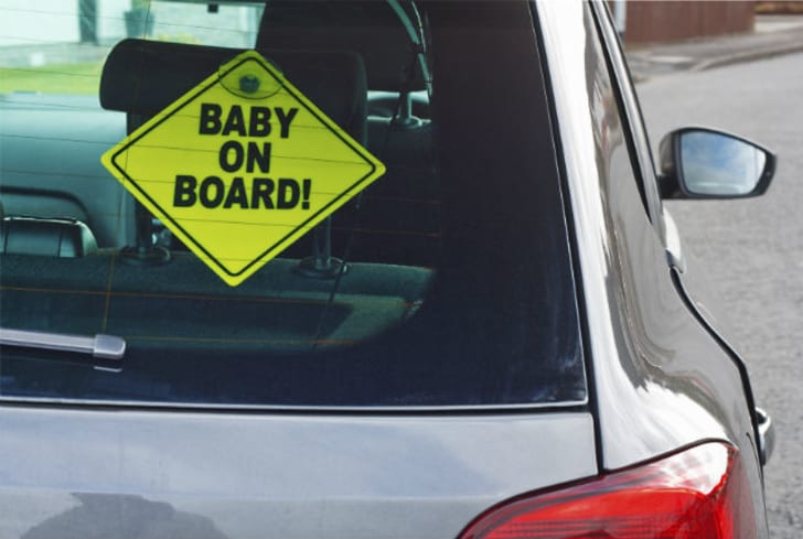 Baby on board sign hangs in the back of a car