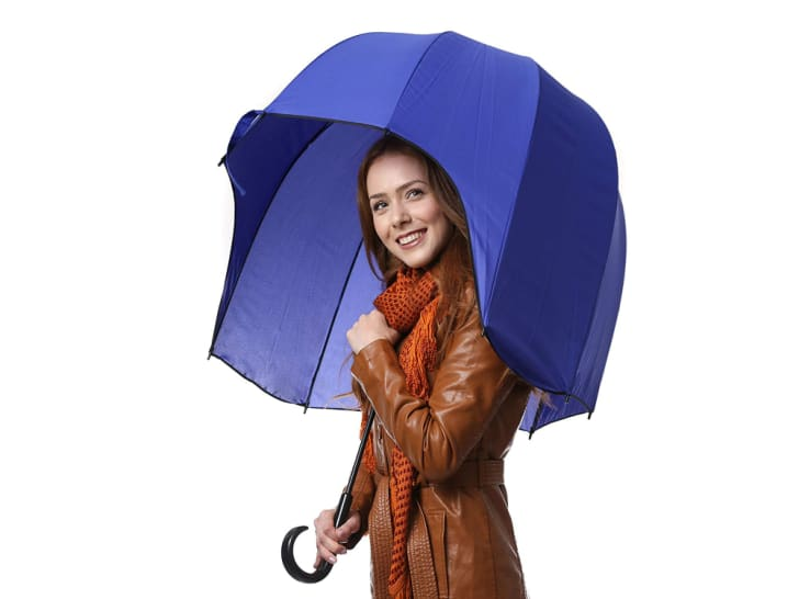 A woman peeks out from under a CloudTen umbrella