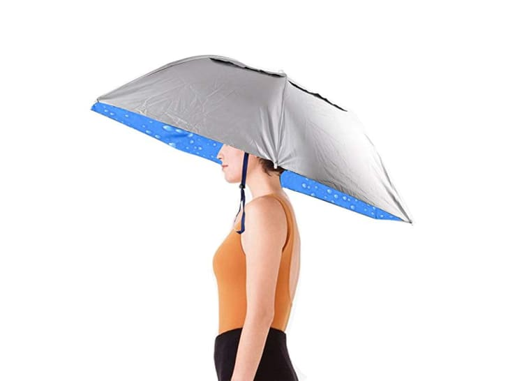 A woman wears a hands-free umbrella on her head