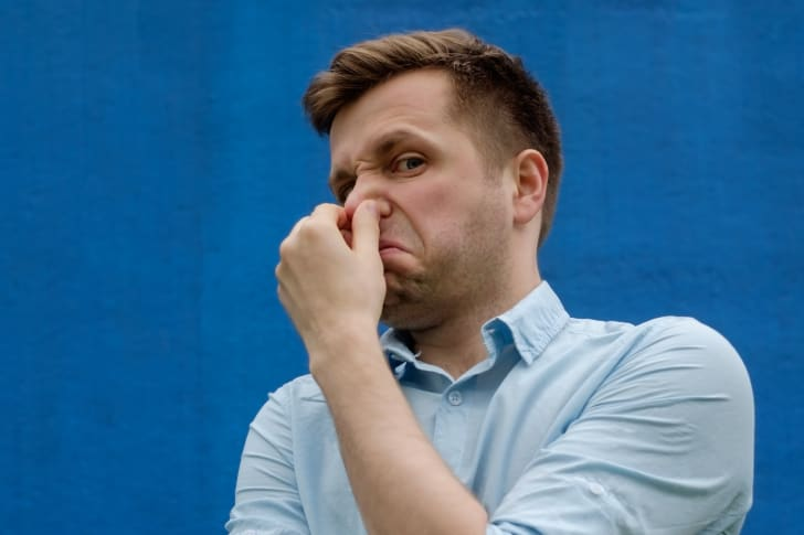 man holding his nose because of terrible smell