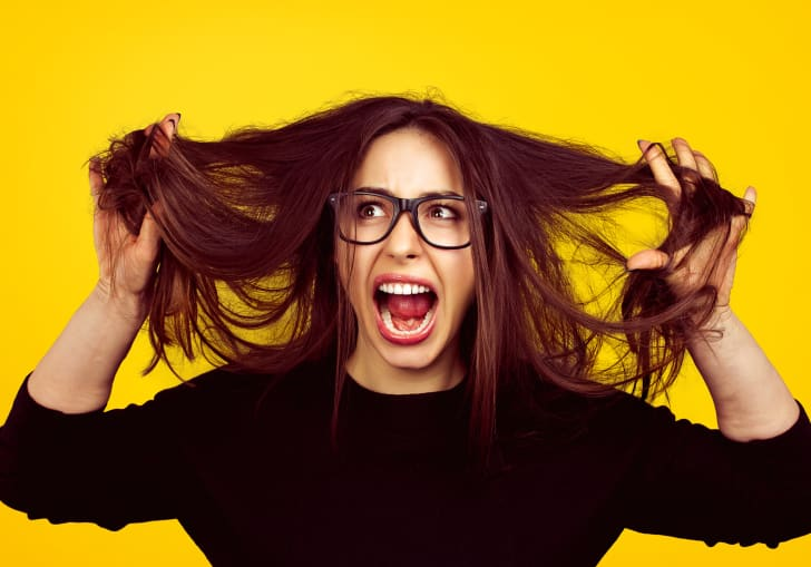 Stressed out young woman pulling her hair out in front of a yellow background