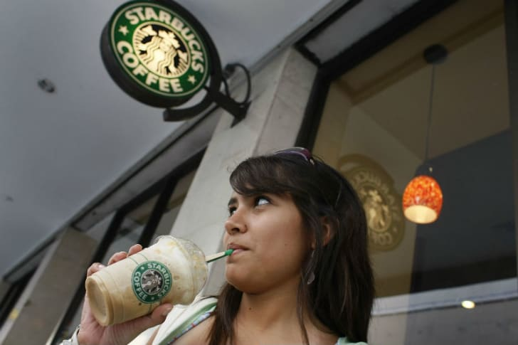 A woman sips from a straw outside of a Starbucks location