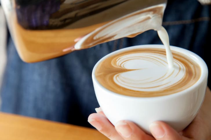 Milk is poured over a cup of coffee in a decorative pattern
