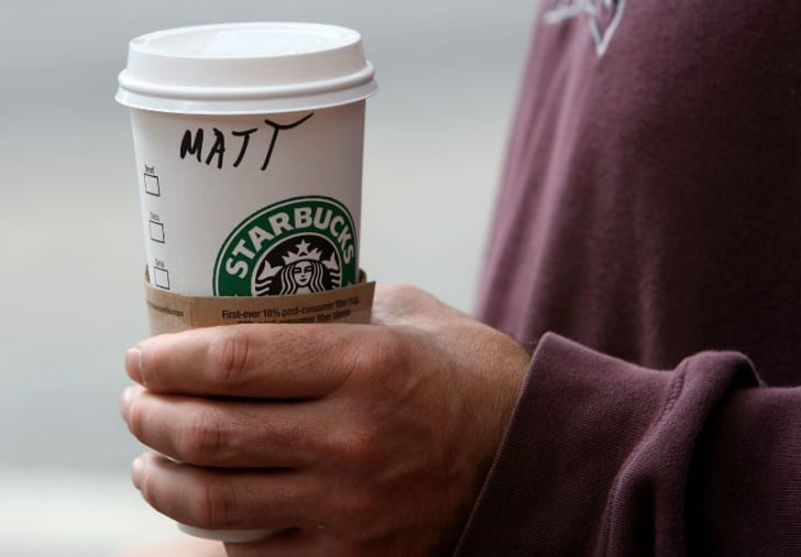 A Starbucks customer holds a coffee cup with their name written on the side