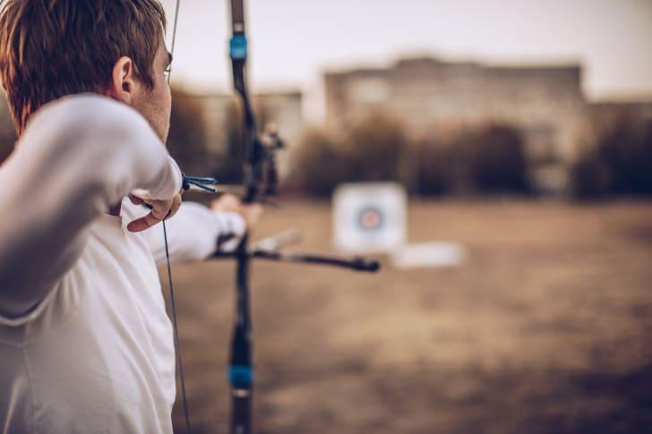 An archer aims an arrow at a target.