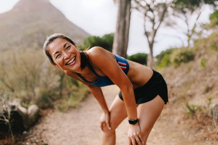 Woman laughing on a running trail.