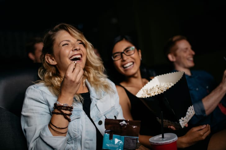 women laughing at a movie