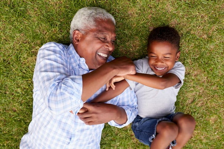 grandfather and grandson laughing on ground