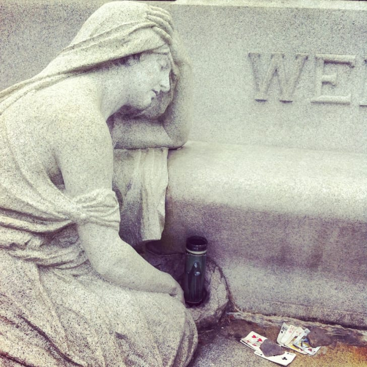 Playing cards near a statue at Houdini's grave in Queens