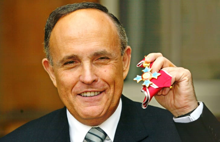 Former New York Mayor Rudolph Giuliani shows of his Knighthood of the British Empire (KBE) medal in 2002.