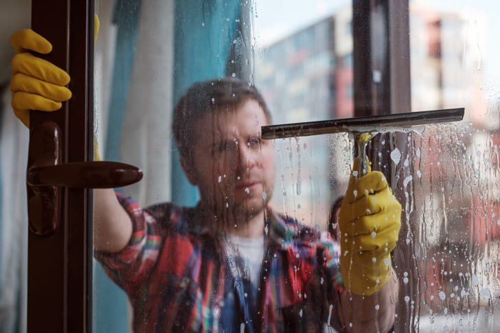 Man cleaning windows on a cloudy day