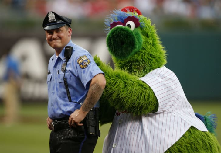 The Phillie Phanatic stands behind a police officer