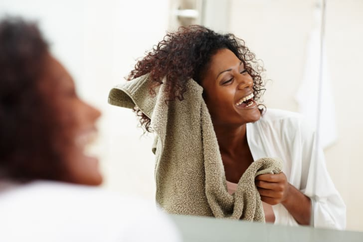 An African-American woman drying her hair with a towel and laughing