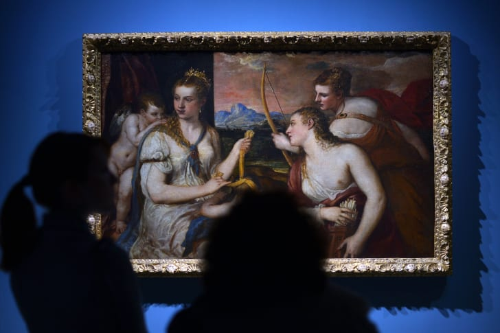 Visitors look at a painting by Renaissance master Titian in Rome