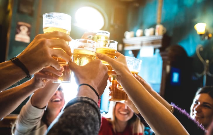 Friends share a celebratory toast with pints of beer