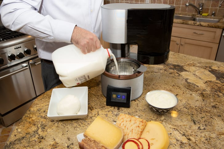 Pouring milk into home cheesemaking machine.