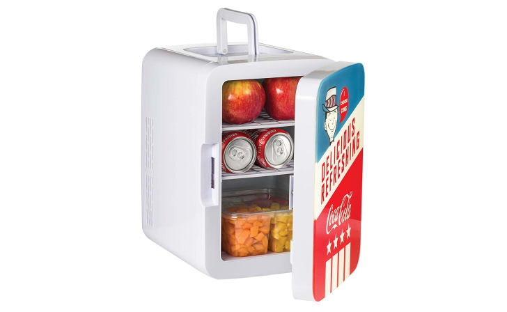 A mini portable fridge open to reveal apples, vegetables, and cans of soda