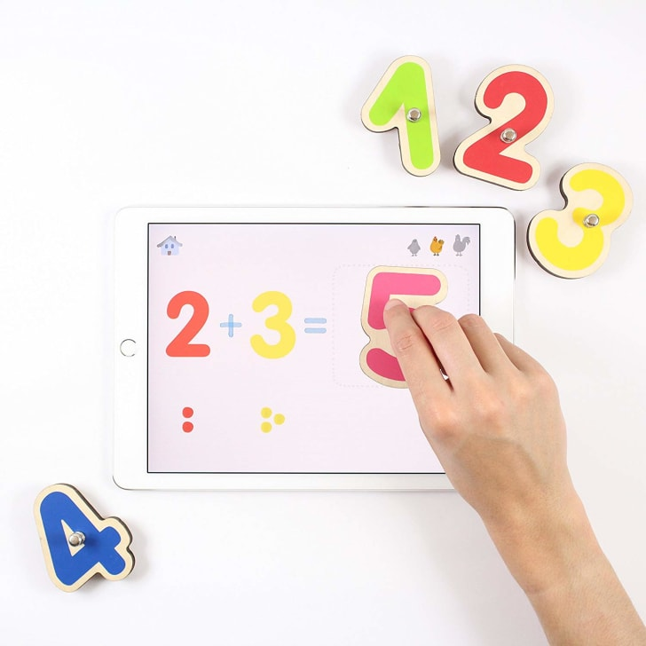 A hand moving wooden numbers around on top of a tablet