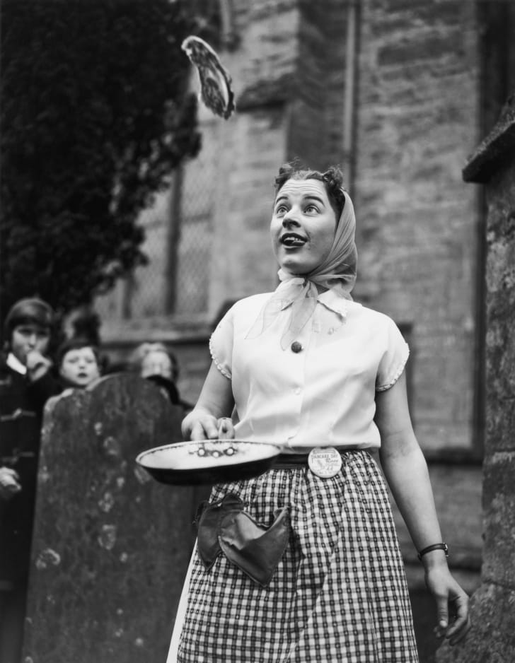Woman flips a pancake from a plate