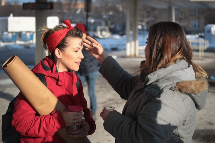 In celebration of Ash Wednesday, a member of the Urban Village Church rubs ashes on the forehead of a commuter outside of a subway station in Chicago in 2018.