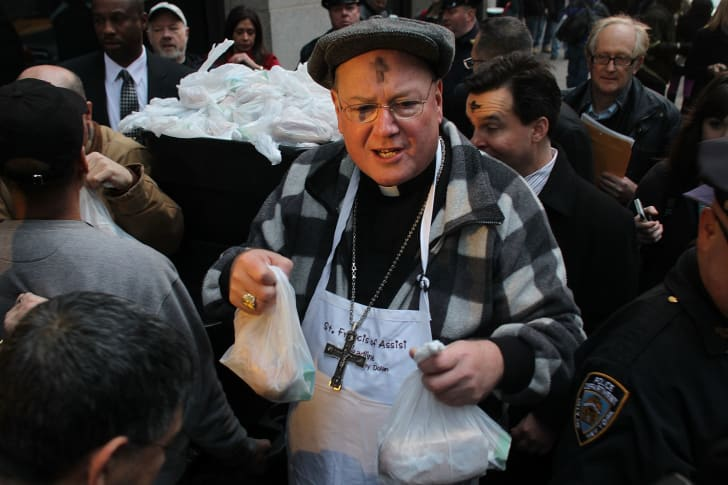 New York's Cardinal Timothy Dolan joins fellow volunteers distributing food at a breadline at St. Francis Assisi on Ash Wednesday in 2012 in New York City.