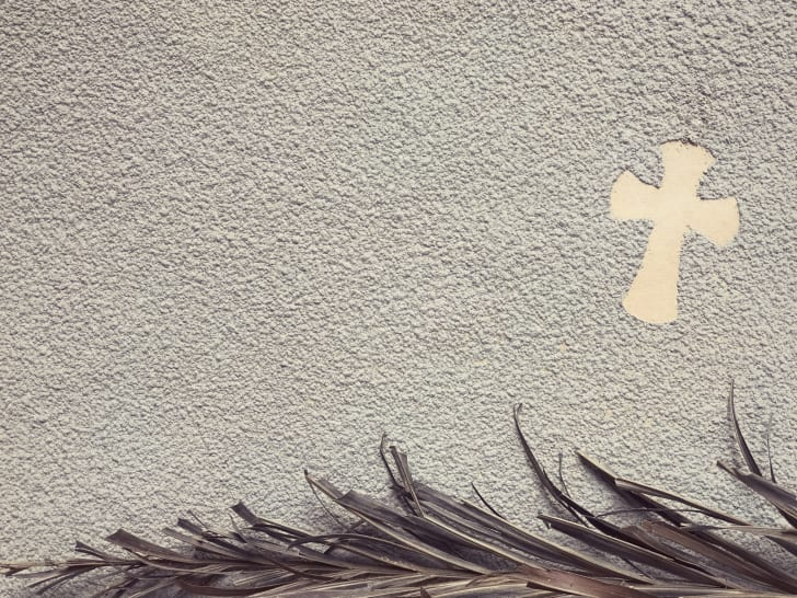 A cross and burned palm leaves in ash.