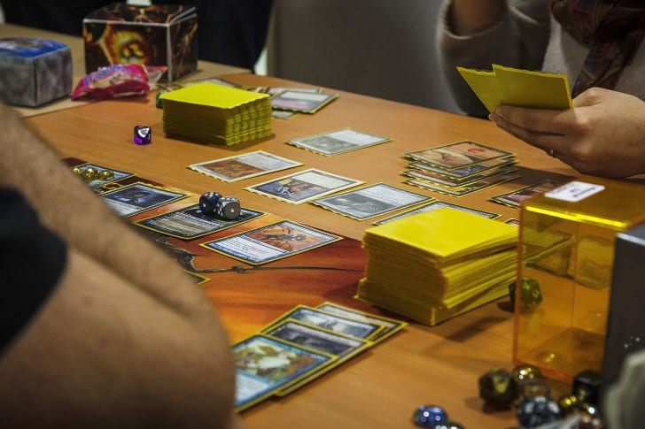 Players at a table playing Magic: The Gathering