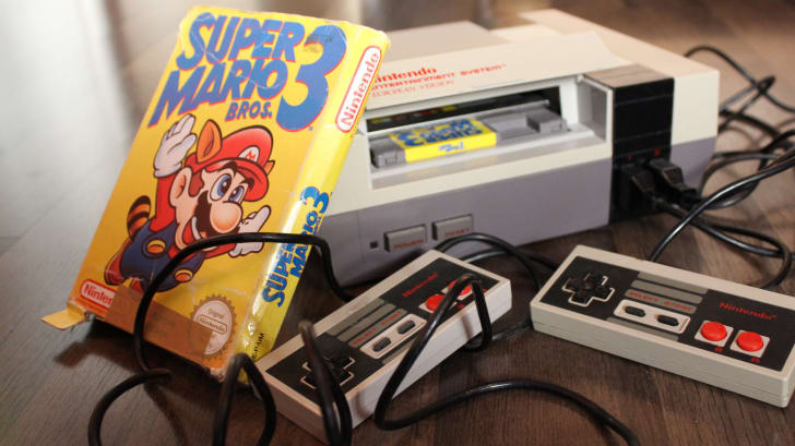 A Super Mario Bros. 3 game next to an NES console