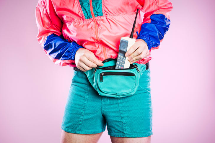 Retro styled man putting a gigantic cell phone into his fanny pack
