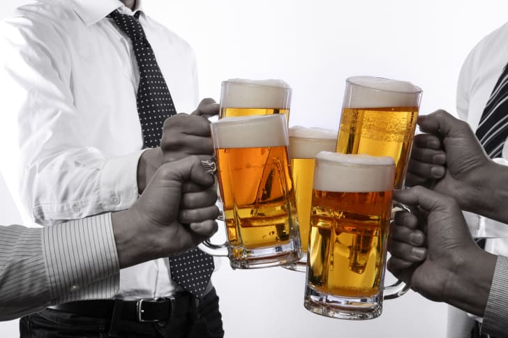 A group of men toasting mugs of beer