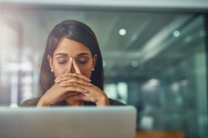 A woman sitting in front of a computer looking tired.