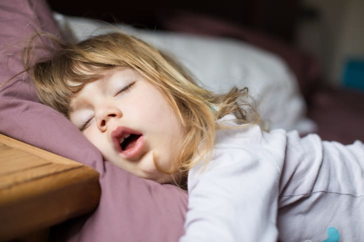 A little girl sleeping with her mouth open.