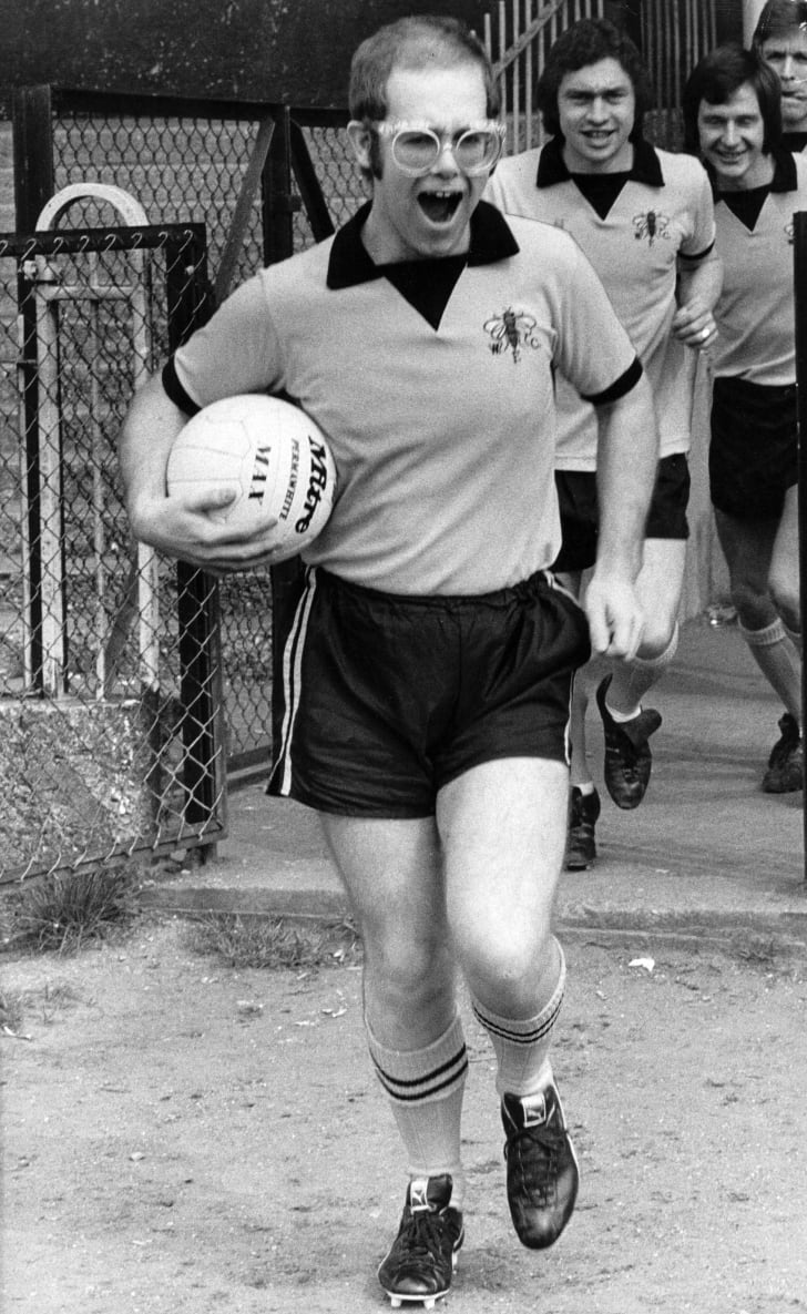 Pop singer and football club chairman Elton John leads Watford Football Club team out onto the pitch in 1974.