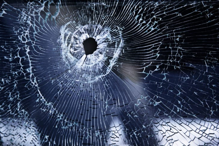 A windshield with a bullet hole is pictured